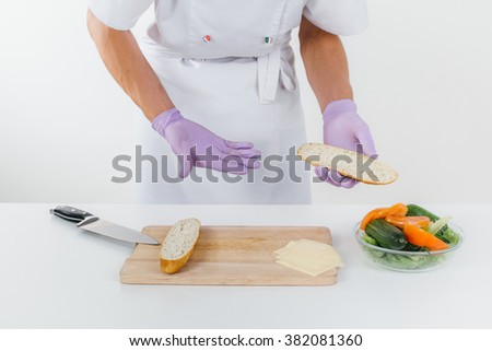 Hands of chef holds bread slice, vegetable salad is on the table in front of chef. Conception of healthy food and healthy lifestyle. Cooking vegetarian sandwich  - stock photo