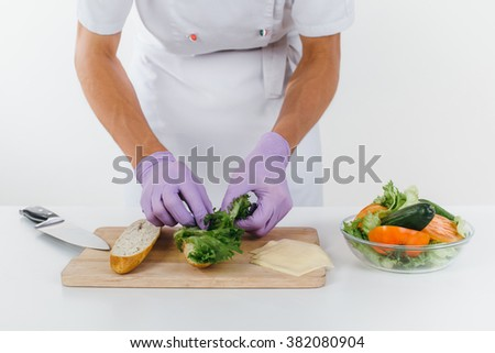 Hands of chef put lettuce leaves on the bread slices, vegetable salad is on the table in front of chef. Conception of healthy food and healthy lifestyle. Cooking vegetarian sandwich  - stock photo