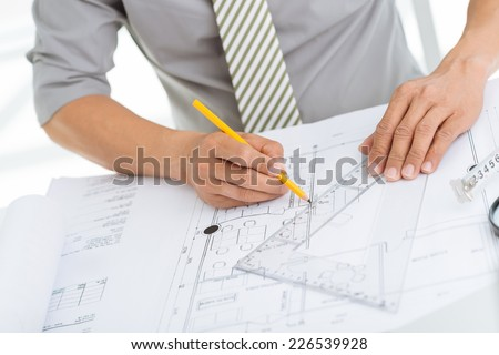 Hands of civil engineer correcting a blueprint - stock photo
