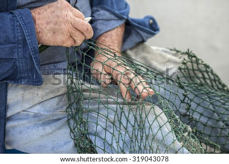 Hands of commercial fisherman mending nets - stock photo