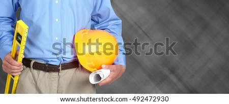 Hands of construction worker with helmet and level.