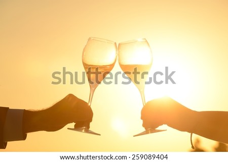 Hands of couple toasting at sunset - stock photo
