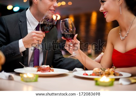 hands of couple toasting their wine glasses over a restaurant table during a romantic dinner. - stock photo