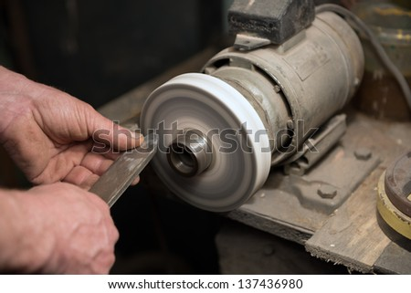 Hands of craftsman are holding a homemade lathe chisel during the sharpening on homemade grinding machine. - stock photo