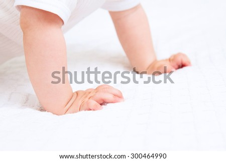 Hands of crawling baby on white background