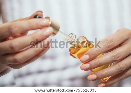 Hands of cropped unrecognisable woman holding cosmetic oil.