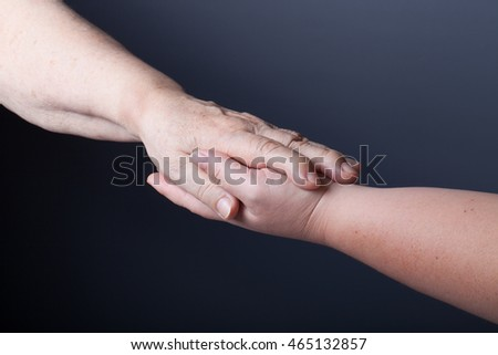 Hands of elderly and young women on black background.