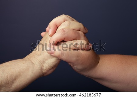 Hands of elderly and young women on black background. Toned.