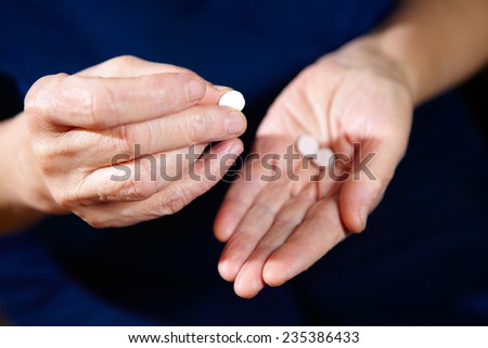 Hands of elderly female with pills. Pharmaceutical background