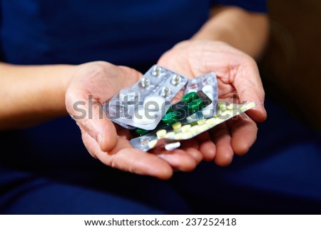 Hands of elderly female with pills. Pharmaceutical background - stock photo