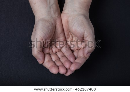 Hands of elderly woman on black background.