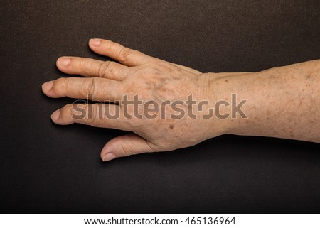 Hands of elderly woman on black background. Toned.