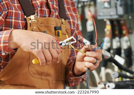 hands of electrician builder engineer worker with electric equipment and wire - stock photo