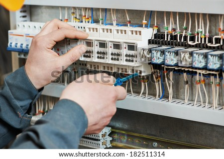 Hands of electrician with screwdriver tighten up switching electric actuator equipment in fuse box - stock photo