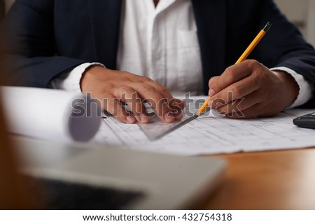 Hands of engineer with ruler checking blueprint