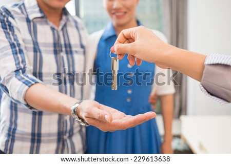 Hands of estate agent giving keys to the couple - stock photo