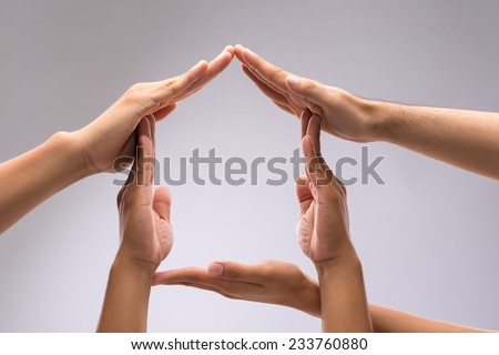 Hands of family members forming house shape