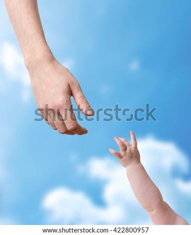 Hands of father and baby stretching to each other.