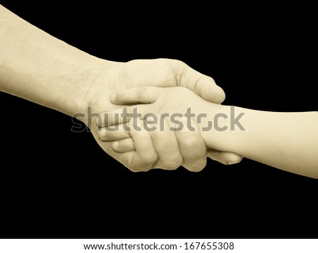 hands of father and son on a black background - stock photo