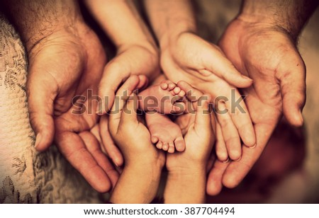 Hands of father, mother, daughter keep little feet baby. Friendly happy family  - stock photo