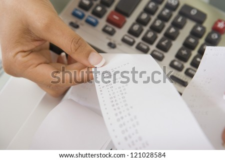 Hands of female accountant with calculator paper tape
