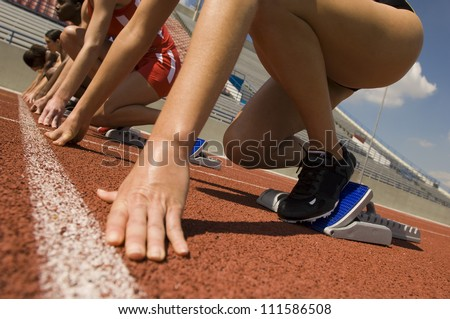 Hands of female athletes at starting line on race track - stock photo