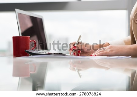 Hands of female bookkeeper working with documents, side view - stock photo