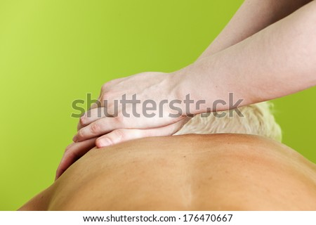 Hands of female massage therapist pressing a woman's shoulders