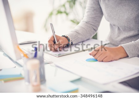 Hands of financial manager taking notes when working on report - stock photo