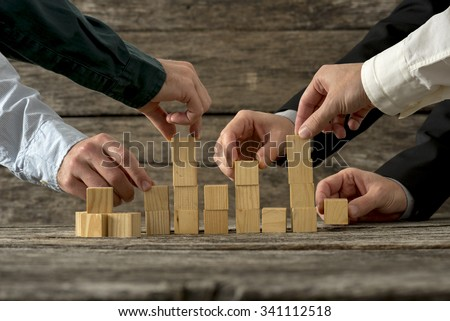 Hands of five businessman holding wooden blocks placing them into a structure. Conceptual of teamwork, strategy and business start up. - stock photo
