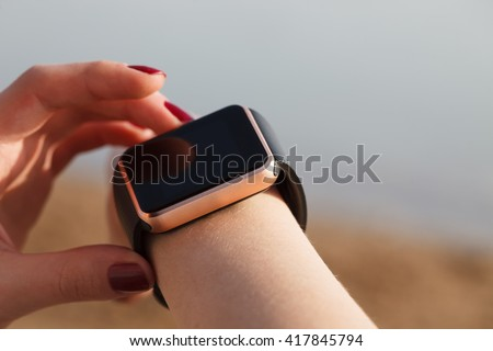 Hands of girl using her modern smart watches outdoors. Trendy wireless technology that let you always stay connected to internet, social media and mail - stock photo