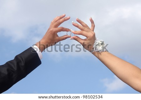 Hands of  groom and  bride hold wedding rings. Against  blue sky.