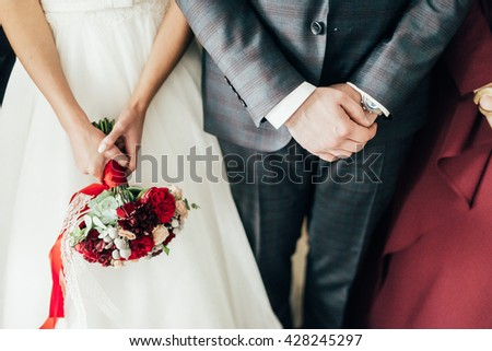 Hands of groom and bride with bouquet