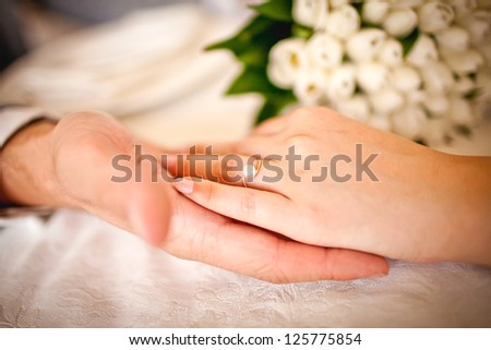 hands of groom and bride with ring, bridal Bouquet - stock photo