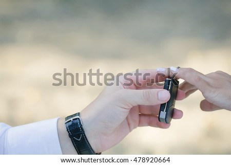 Hands of groom puts keyless entry system on chain on bride finger during wedding ceremony on natural background
