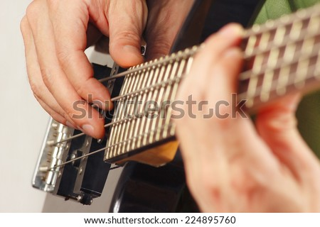 Hands of guitarist playing the electric bass guitar closeup - stock photo