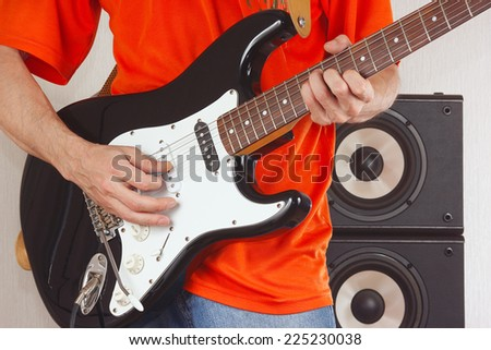 Hands of guitarist playing the guitar closeup - stock photo
