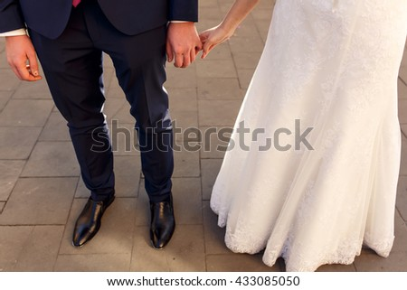 hands of happy bride and groom holding each other close-up at wedding ceremony