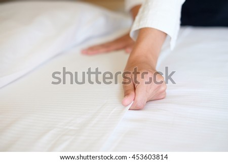 Hands of hotel maid making a room bed - stock photo