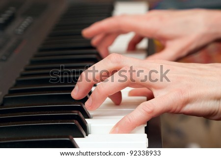 hands of keyboard player on keys of synthesizer