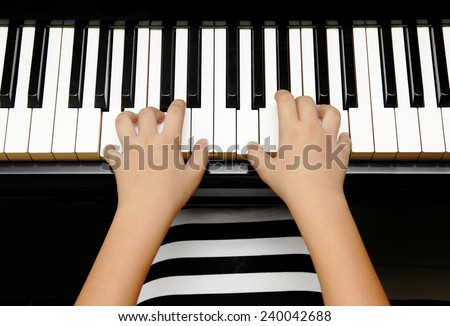 hands of kid playing piano - stock photo
