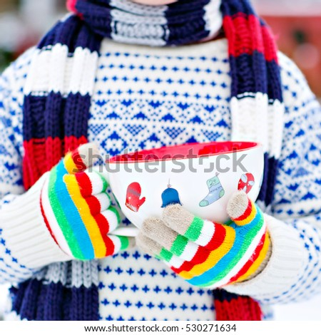Hands of little child holding big cup with snowflakes and hot chocolate drink and marshmallows, outdoors with snow background. Kid boy in winter sweater, hat, long warm scarf and colorfull gloves.