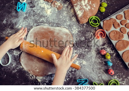 Hands of little girl sheeting dough with rolling pin. Easter baking preparation. Close-up of child's hands with a rolling pin baking Easter cookies. Easter food concept. Top view. - stock photo