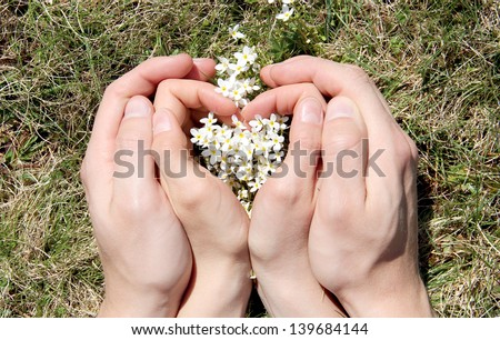 Hands of lovers couple in shape of heart - stock photo