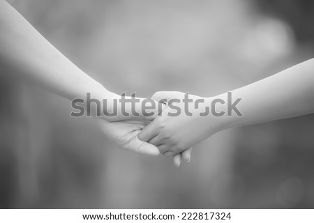 Hands of lovers, men and women in monochrome, soft focus - stock photo