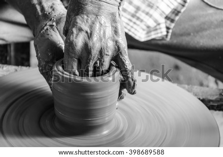 Hands of making clay pot on the pottery wheel ,gray-scale,select focus, close-up. - stock photo