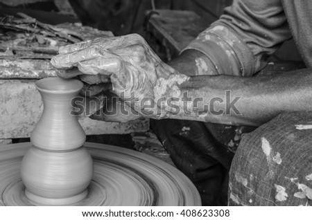Hands of making clay pot on the pottery wheel ,grayscale,select focus, - stock photo
