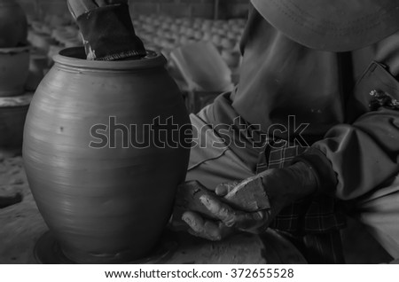 Hands of making clay pot on the pottery wheel ,grayscale,select focus, close-up. - stock photo