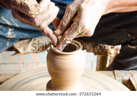 Hands of making clay pot on the pottery wheel ,select focus, close-up. - stock photo