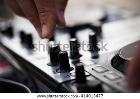 Hands of male Dj playing music on modern midi controller turntable. Digital device for mixing music on events and in studio.